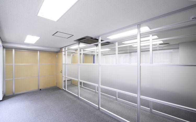 アルミ素材の明るい木目パーティションとガラスのパーティションのオフィス事例