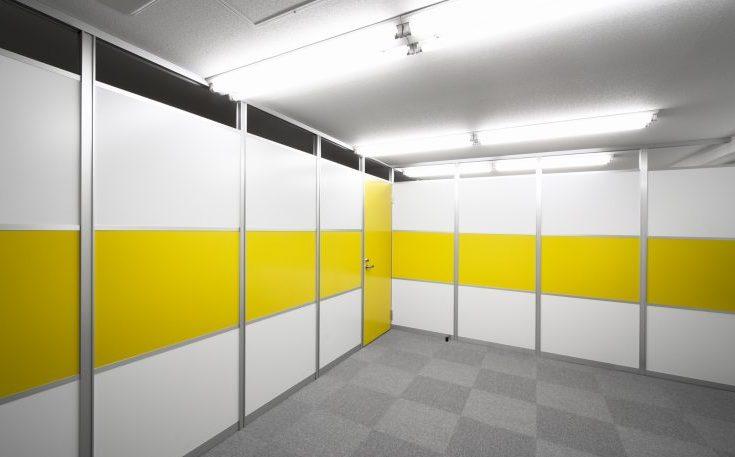 アルミ素材の白いパーティションと黄色のパーティションとドアのオフィス事例