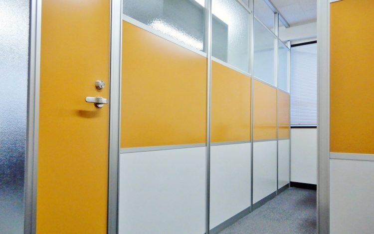 アルミ素材の白いパーティションと黄色いドアとパーティションとガラスのパーティションのオフィス事例
