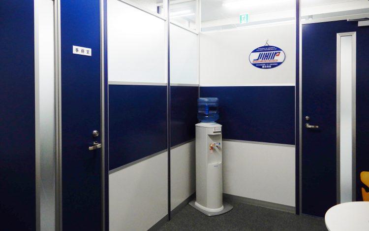 アルミ素材の白いパーティションと青いドアとパーティションのオフィス事例
