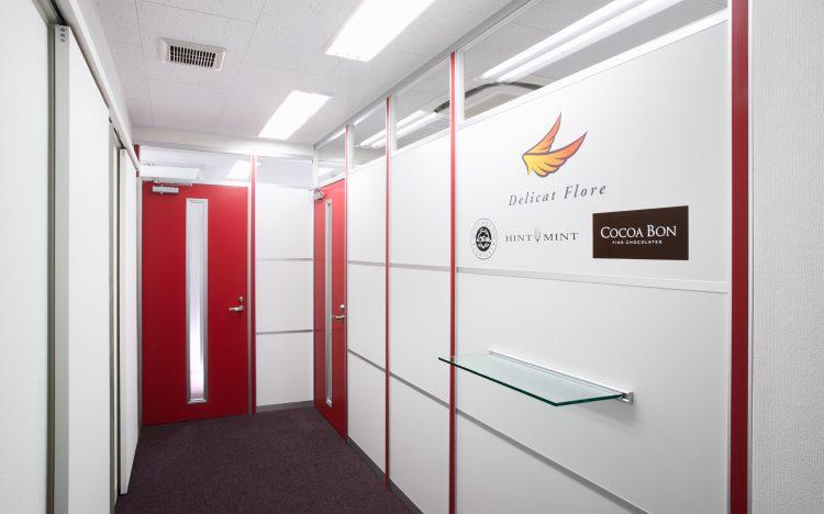 アルミ素材の白いパーティションと赤いドアと赤いポストカバーを使ったオフィスエントランスの事例