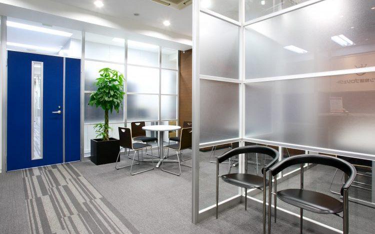 アルミ素材の青いドアと曇りガラスのパーティションのオフィスエントランス事例